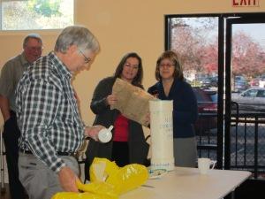Pastor Brenda and Moderator Barbara Swint examine one of the time capsule's treasures.