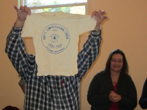 John Hollowell holds up a centennial shirt that had been packed in the time capsule.